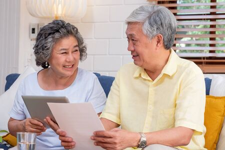 Asian senior couple use tablet searching about retirement financial document sitting on sofa at home,senior learn to use technology.aging in place concept Stok Fotoğraf