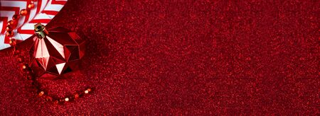 Merry christmas and happy new year red background.top view of tinsel,gift box,ball,ribbon decorate on sparkling table.holiday celebration greeting card.banner panoramic mockup for display of design Stock Photo