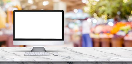 Blank screen desktop computer on marble table top with blur people shopping at supermarket bokeh background,Mock up for display or montage of design