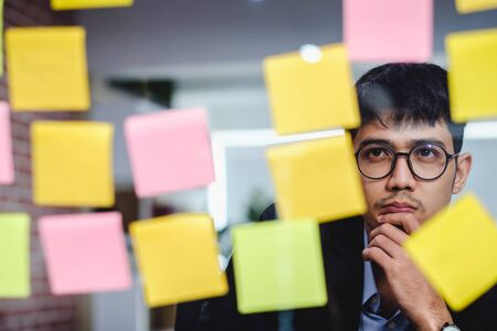 asian businessman looking and writing on sticky note for brainstorming ideas on clear whtieboard at modern office. analyze and synthesis