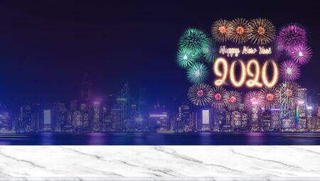 Gelukkig nieuwjaar 2020 vuurwerk boven stadsgezicht 's nachts met leeg marmeren tafelblad, panoramische banner mock-up sjabloon voor weergave of montage van product voor reclame voor vakantiepromotie Stockfoto