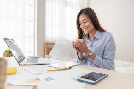 Asian businesswoman drinking coffee and while working with laptop on table in bedroom at home.Work at home concept.work from home concept Banco de Imagens