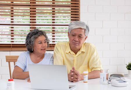 Asian couple seniors use laptop video conference with doctor about illness and prescription pill in living room at home.Healthy lifestyle.aging at home concept