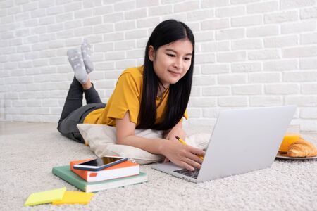 Asian female freelancer working on laptop computer at home.woman lying down on carpet at brick wall.working online lifestyle