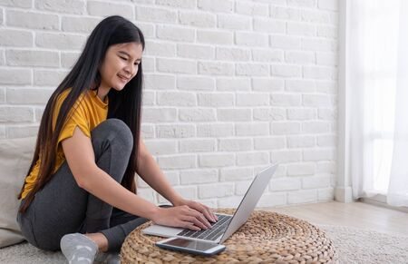 Asian female sit with knees up on floor using laptop on wicker stand near window in living room at home.Work at home concept.work from home.relax lifestyle