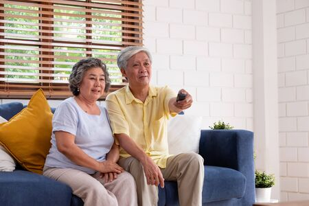 Asian couple senior sitting on sofa and use remote control to change channel and watching tv in living room at home.panning from blur foreground television. 写真素材