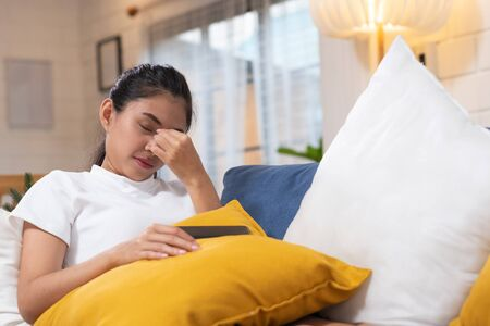 Young asian woman feeling  stress  and closed eyes  suffering from headache and lying down on sofa in living room, tired  female office worker massaging eyes Stok Fotoğraf