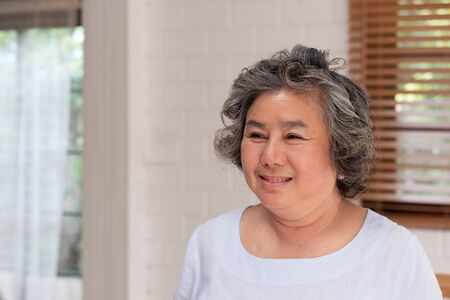 Asian senior woman smile in living room at home, Happy aging at home concept