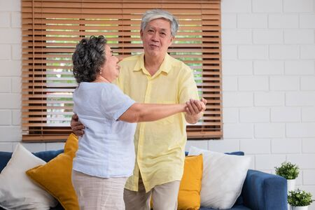 asian seniors couple enjoy dancing in living room at home. aging at home concept 스톡 콘텐츠