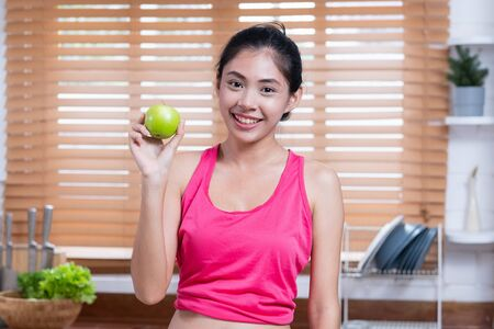Young Asian blogger holding apple and telling about healthy Food, while recording video on camera at home. media influencer reviewing and marketing concept