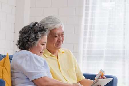 Asian senior couple use tablet video conference with doctor about pill  while sitting on sofa at home, senior learn to use technology. aging at home