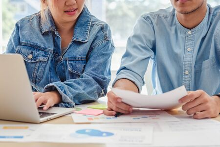 Asian creative designer team casual meeting and brainstorming on desk with paperwork and online data on laptop in meeting room at modern office. business planning concept Stock Photo