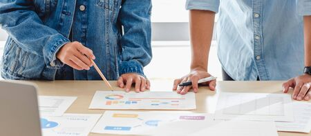 close up hand creative designer team casual meeting and brainstorming on desk with paperwork and online data on laptop in meeting room at modern office.business planning concept Stock Photo