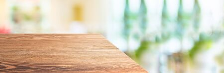 wood table top product display background with blur people in green cafe restaurant. left perspective wooden kitchen counter. Banner mockup presentation for your product online