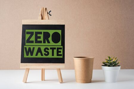 zero waste word on blackboard with paper cup and green plant on white table and brown background. eco friendly concept