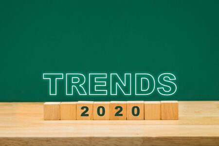 trends 2020 idea on wood cube block on table with green blackboard.business forecasting concept