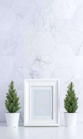 white vintage photo frame with christmas tree,pine cone and decor xmas ball on white table and marble tile wall background.clean minimal simple style.holiday still life mockup to display design