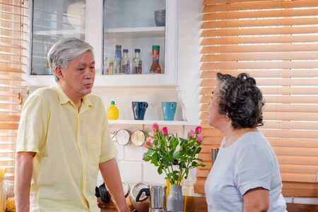 Asian Senior couple husband and wife discussing future plan after retire in kitchen at home .lovely senior couple concept