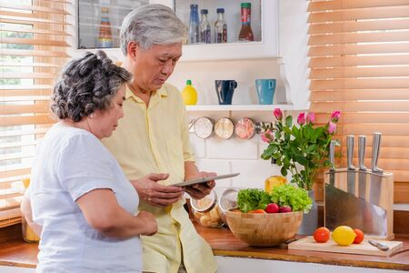 Asian senior couple using tablet computer to searching menu recipe and type of vegetable in kitchen at home.senior with technology lfiestyle.aging at home Stock Photo