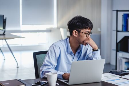 asian businessman get stress and thinking when working with laptop on desk at modern office.business fail concept.man rest hand on chin on table when stuck out of idea