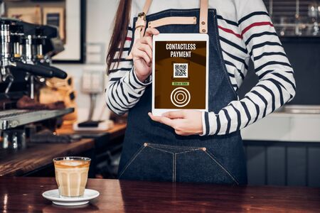 CLose up woman barista hand holding tablet with contactless payment method at counter bar in restaurant cafe.online payment