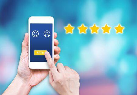 Klicken Sie mit der Hand auf die Bewertung auf dem Handy, um die Zufriedenheit des Dienstes online zu gewährleisten. Kundenbewertungserfahrung des Dienstes Standard-Bild