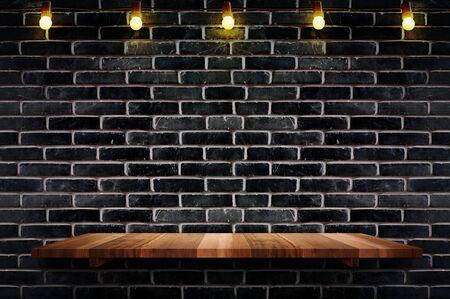 Estante de madera de tablón marrón vacío en el fondo de la pared de ladrillo negro con cadena de bombillas, maqueta para exhibición o montaje de producto o diseño.