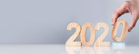 Close up hand pick 2020 business trends down on white table and grey background.holiday celebration.banner copy space for adding text