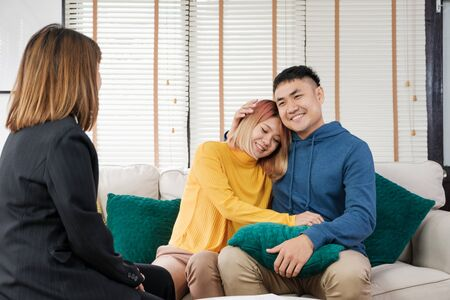 Asian happy couple buying new home with realtor agent with smiling face at new home.buying new house real estate