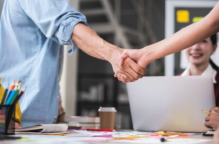 close up handshaking of ux developer and ui designer deal with contract partnership over meeting table in boardroom at modern office.congratulation handshaking for job promotion