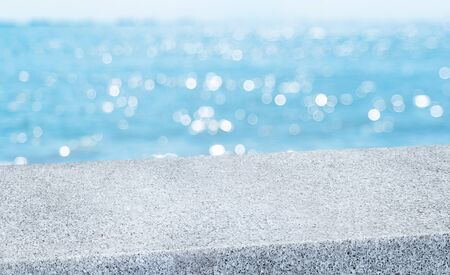 summer background.Empty diagonal grey pebble stone table with blur sea and sky boekh background,banner mockup template for display of product