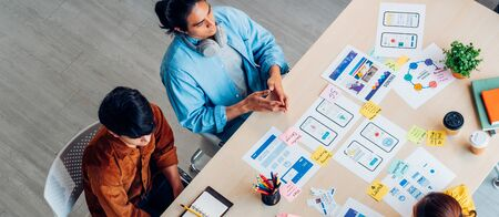 Top view asian ux developer and ui designer brainstorming about mobile app interface wireframe design on table with customer breif and color code at modern office.Creative digital development agency