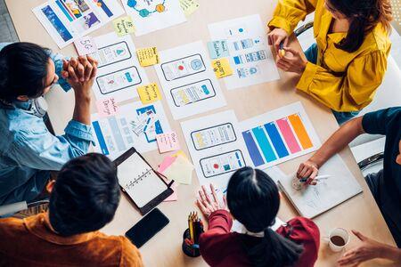 Draufsicht asiatischer UX-Entwickler und UI-Designer Brainstorming über das Wireframe-Design der mobilen App-Schnittstelle auf dem Tisch mit Kundenbrief und Farbcode im modernen Büro. Agentur für kreative digitale Entwicklung