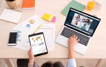 une femme asiatique travaille à domicile avec une application de vidéoconférence collaboration avec des collègues avec un graphique d'entreprise sur une tablette. Banque d'images