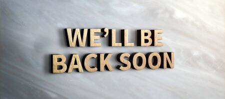 we will be back soon wood sign on marble wall.business under construction concept.3d rendering text Фото со стока