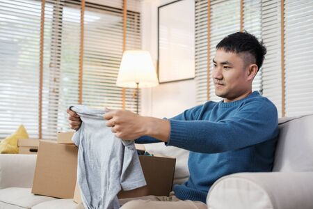 asian man open cardboard boxes  while moving to new home at sofa in living room.unpacking for new house