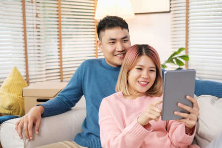 happy asian couple using tablet to design decorate new house interior at sofa when finish moving box in house