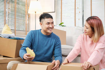 Happy asian couple open cardboard boxes  while moving to new home at sofa in living room.unpacking for new house