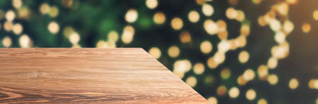 wooden table top with abstract blur christmas tree with string light background with bokeh light,winter Holiday backdrop,Mock up banner for display of product