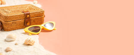 summer sand beach with wicker bag and sunglasses on peach vintage color background.vacation banner mockup 写真素材