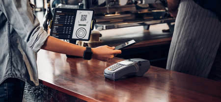 customer contactless payment for drink with mobile phon at cafe counter bar,seller coffee shop accept payment by mobile.new normal lifestyle concept