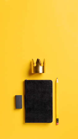content is king for online marketing concept.top view of black notebook with golden crown and pencil on yellow table background,vertical banner for advertising on mobile media
