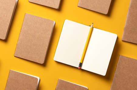 content marketing concept,.top view of hand writing on open notebook and yellow pencil align with kraft paper book in pattern on yellow table background.mockup for advertise content online