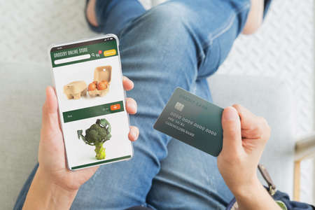 close up hand of woman order grocery online store with mobile and pay contactless with credit card at home.new normal digital lifestyle with technology