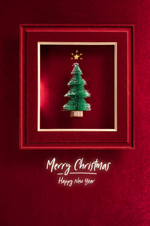 Merry Christmas and happy new year text and Christmas tree in felt photo frame on velvet red felt fabric  top view background 写真素材