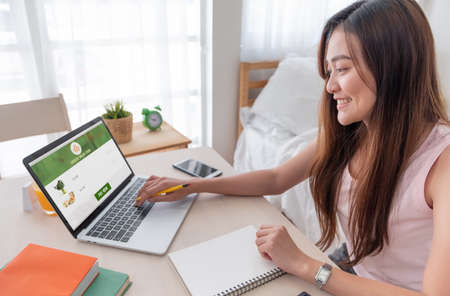 Asian woman order grocery online with laptop at home.new normal digital lifestyle with technology