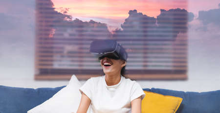 asian woman use virtual reality glasses travel virtual at mountain sunrise scene by sitting on sofa at home.digital lifestyle with technology