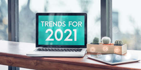 Trends for 2021 in laptop computer screen with icon floating on tablet on wood stood table in at window with blur background,Digital Business or marketing trending