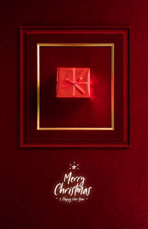 Merry Christmas and happy new year glowing with Red Christmas gift in picture frame on velvet red felt fabric wall.winter holiday background 写真素材