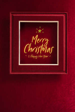 Merry Christmas and happy new year glowing with star in picture frame on velvet red felt fabric wall.winter holiday background 写真素材